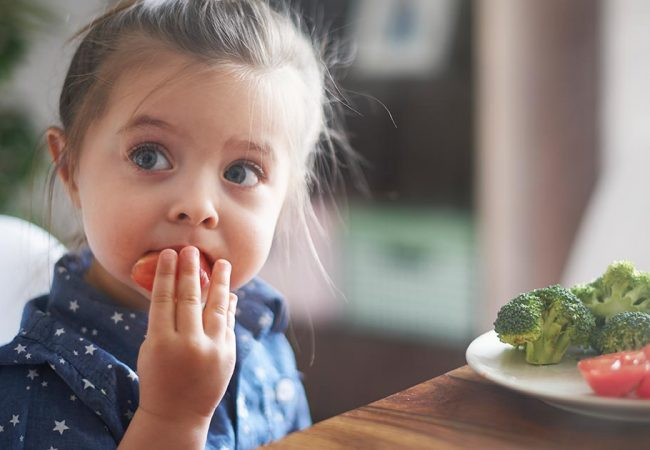 Young girl eating healthy vegetables at the dinner table