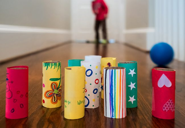 A kid bowling with DIY toilet paper roll pins