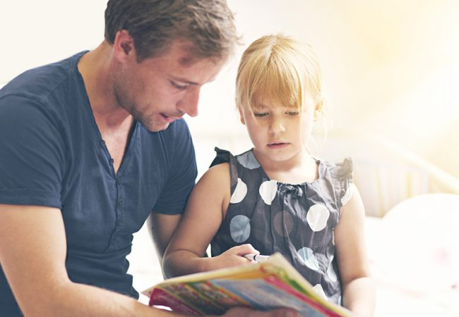Father reading a book about natural disasters to his daughter