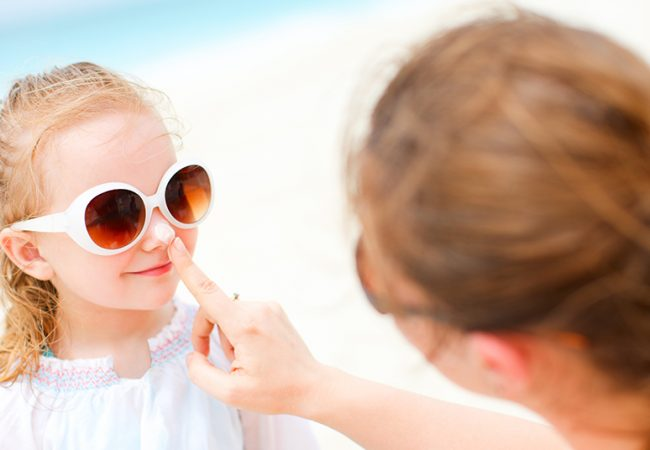 Mother putting sunscreen on a young girl's nose
