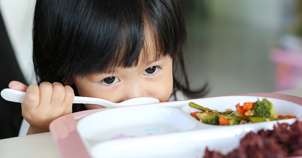 Young girl eyeing her vegetables