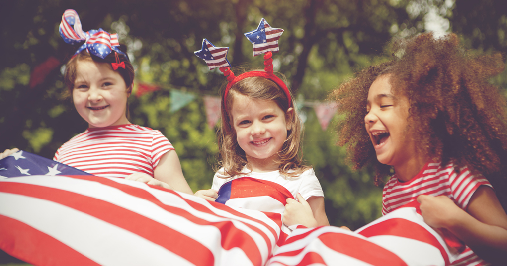 A group of young children playing on the fourth of July with an American flag