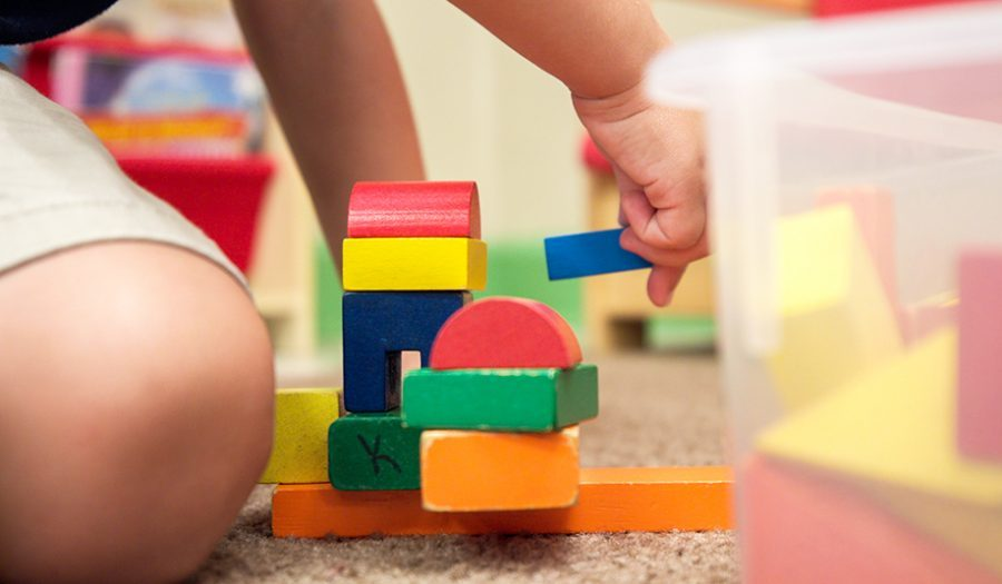 Preschooler stacking toy building blocks to build teamwork skills