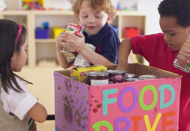 Children placing canned food in a box that reads FOOD DRIVE
