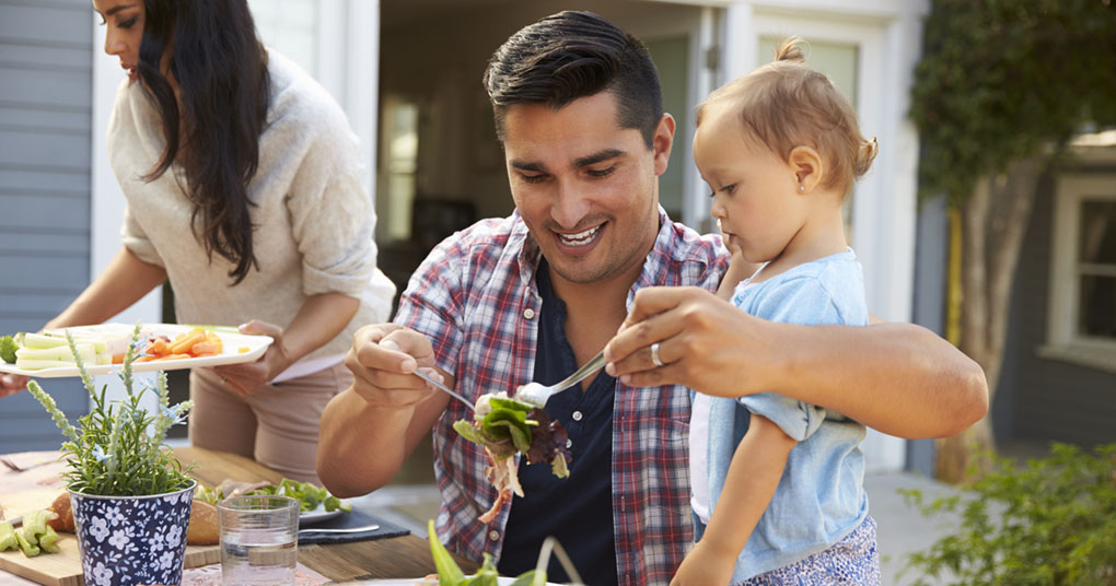 A father serves a family-friendly summer dinner recipe to a young child.