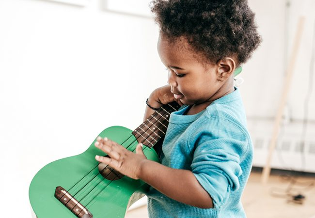 Toddler plays with a green guitar as part of his early musical development.