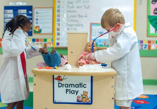 Two preschoolers pretend to be doctors and play with dolls as they develop executive function skills.