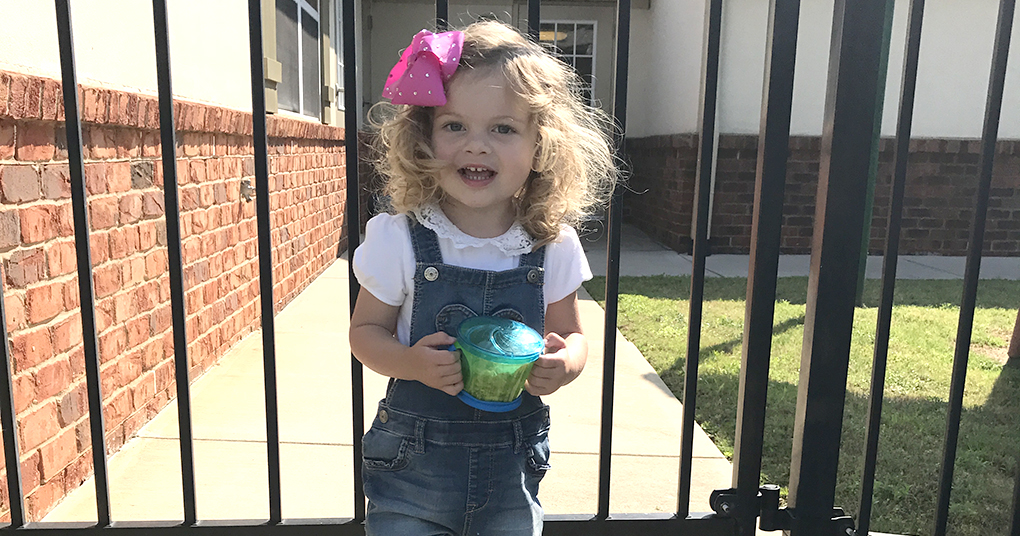 A 2-year-old girl stands outside her preschool building on the first day of school.