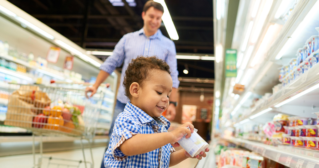 A preschooler enjoys easy activities while grocery shopping with his father.