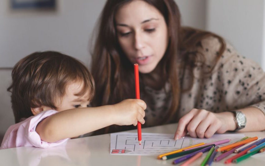 Mom helps her young child complete a printable safety activity.