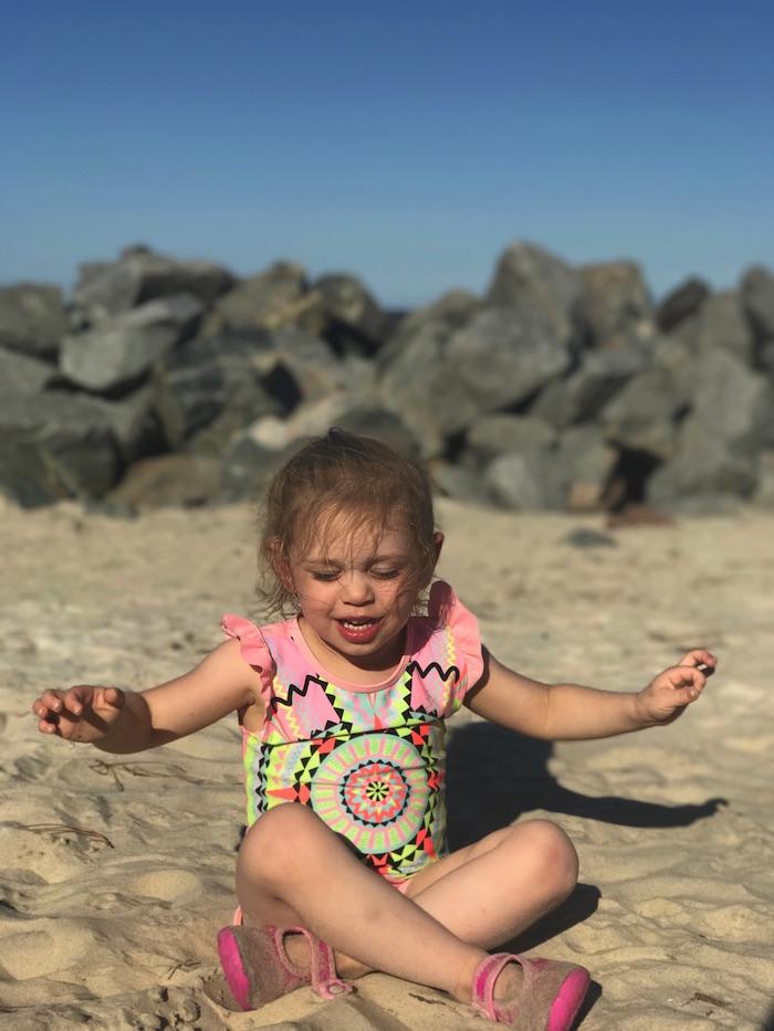 Preschool girl meditating on the beach.