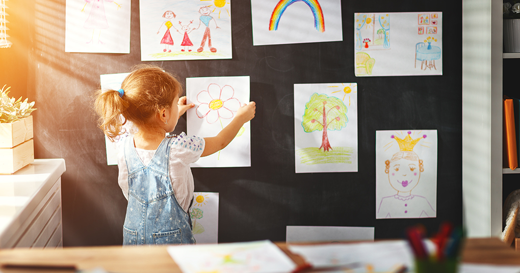 Little girl hangs her art up on a wall as part of her art gallery at home.