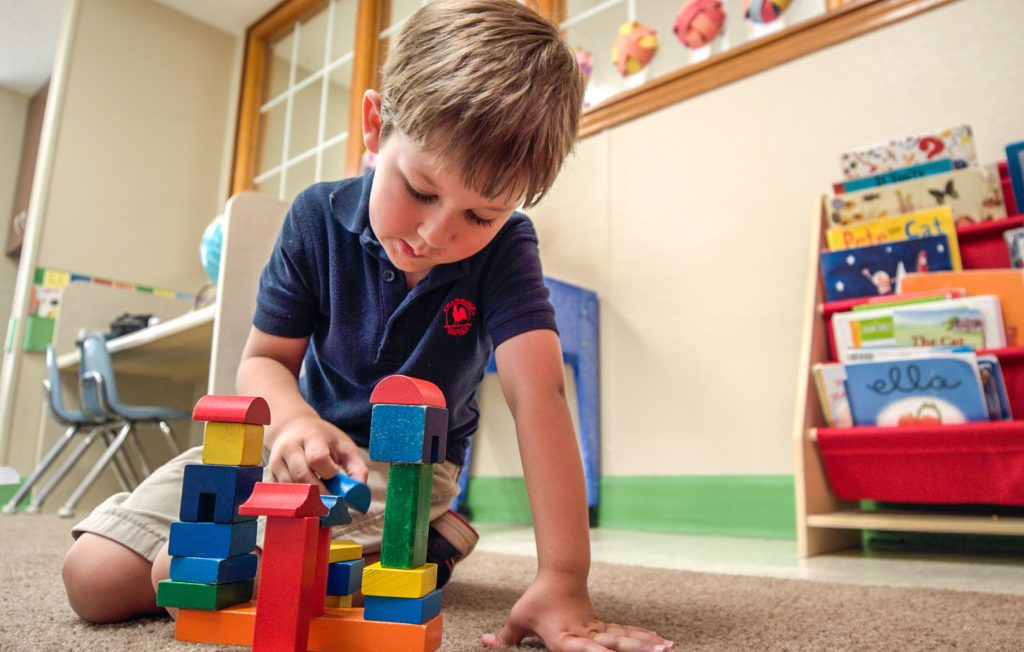 Young boy playing with blocks and learning about problem solving