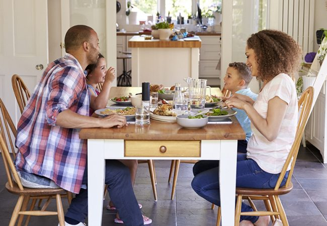 Family with Young Children At Home Eating Meal In Kitchen Together