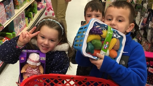 Three young children at a grocery store purchasing gifts