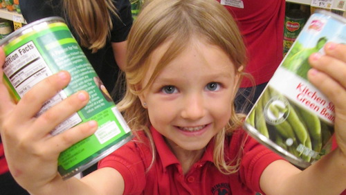 Young girl grocery shopping for families in need for Thanksgiving, holding two cans of green beans