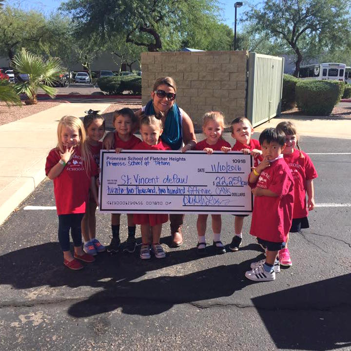 Primrose students and teacher present a check to a local charity