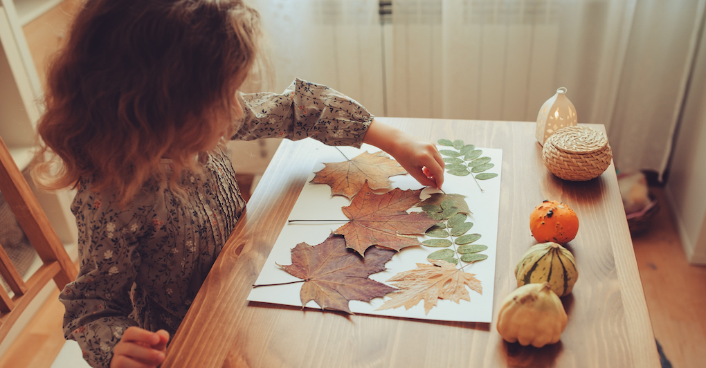 Little girl sitting at table creates fall craft with leaves and construction paper