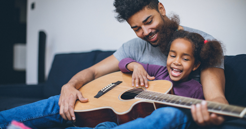 Dad and daughter play music together on guitar