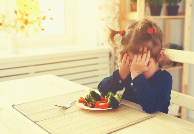 A young picky eater refuses to eat her vegetables