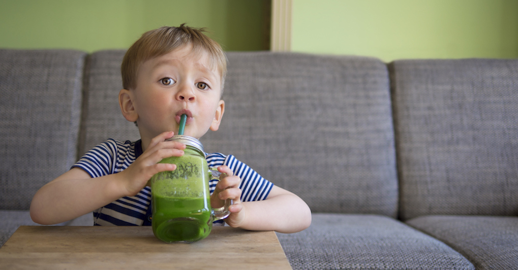 toddler drinking a green smoothie