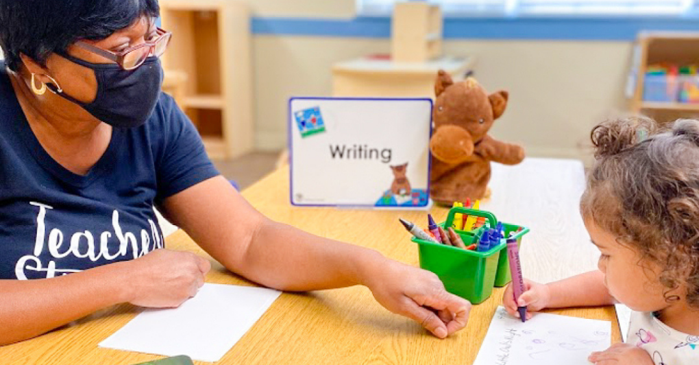 Teacher with mask helping a student at writing center