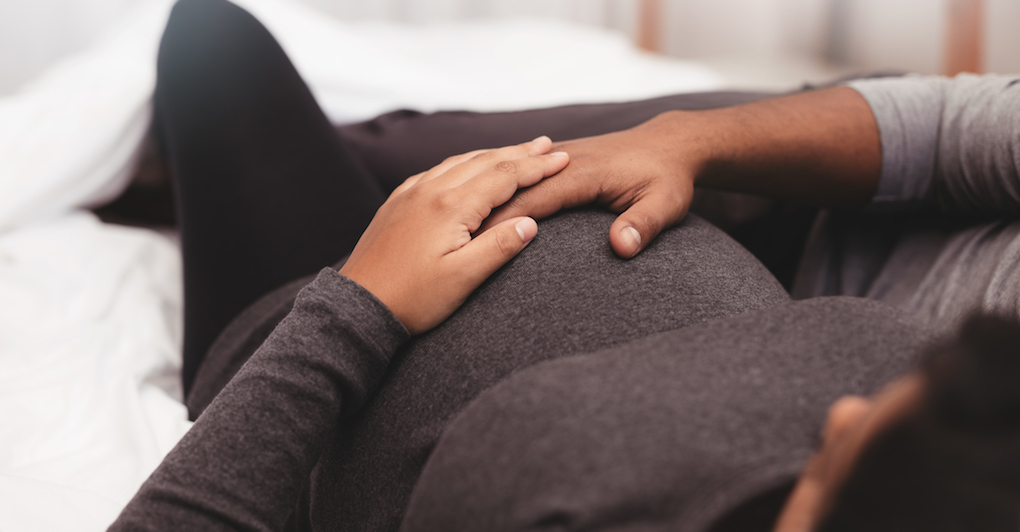 Close up of pregnant couple lying on bed at home. Focus on hands of man and woman on a pregnant belly.