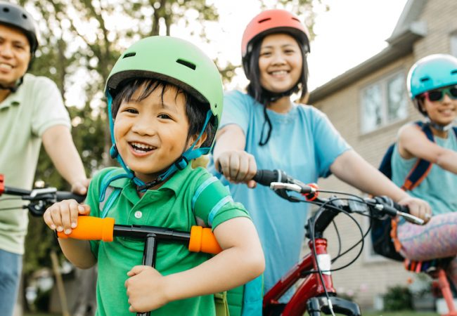 Family of four smiling riding bikes and wearing helmets