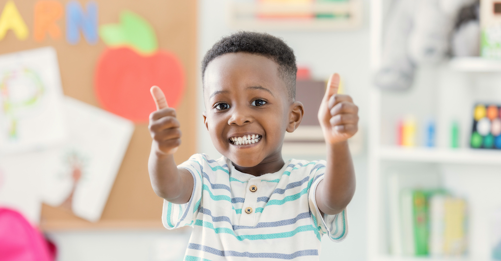 Little boy at preschool smiles and gives thumbs up to camera on back to school