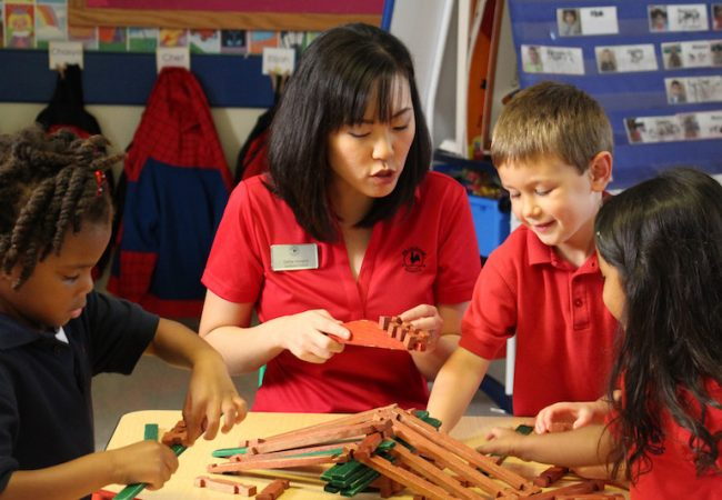Primrose teacher helps preschool students build and play in classroom