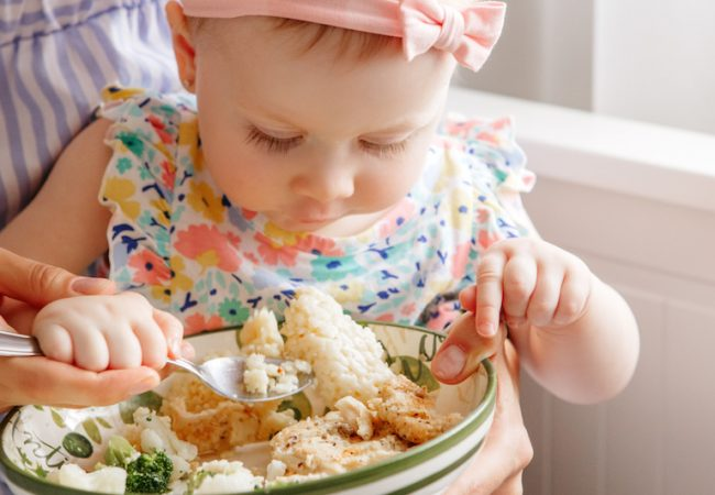 Little baby girl eating vegetables and cauliflower off of plate