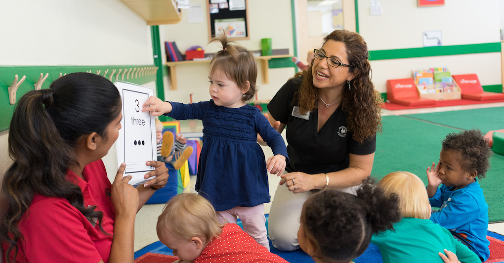 Primrose teachers interact with toddlers in the classroom and help them learn