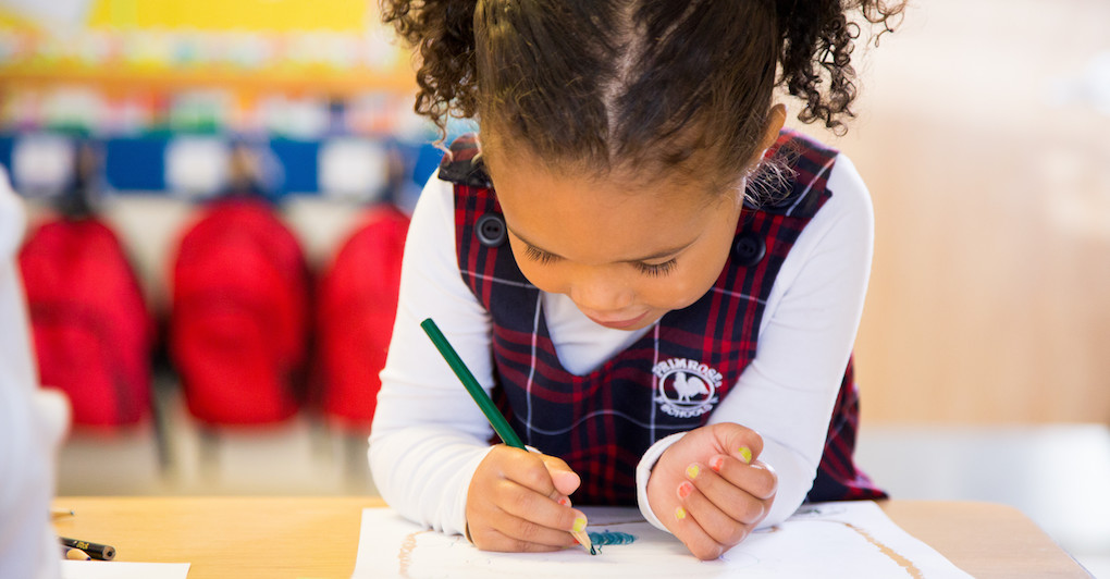 Child in Primrose uniform colors a picture in the classroom