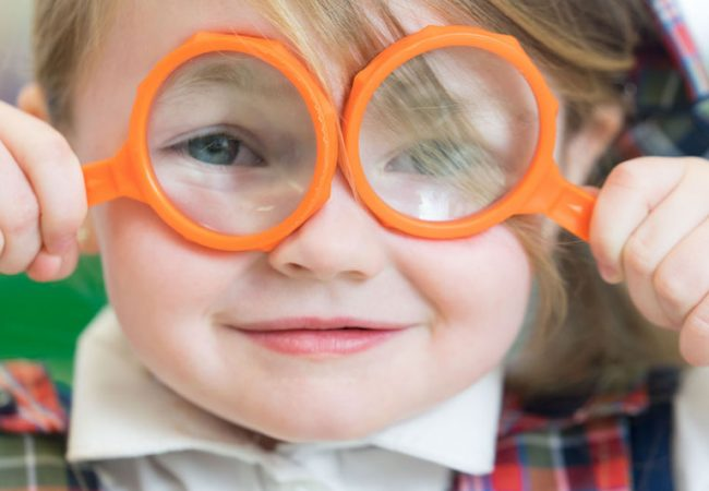 Little girl in Primrose outfit holds magnifying glasses to her eyes for a science experiment at preschool