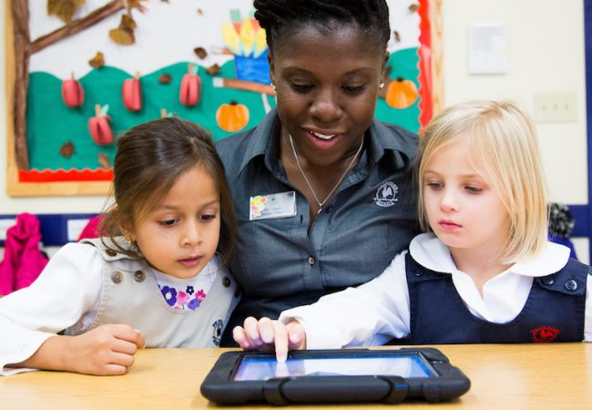 Primrose teacher sits at table and helps two girl preschoolers use tablet