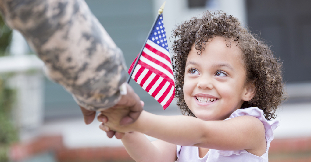 Little girl holds American flag and hand of woman in military uniform for Veterans Day