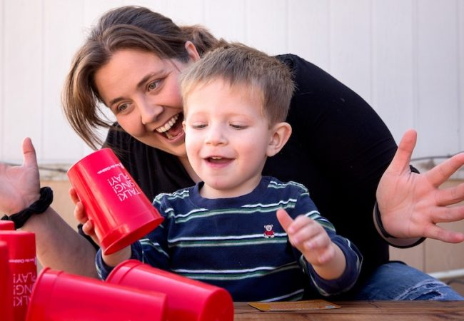 Woman plays with young boy stacking red cups.