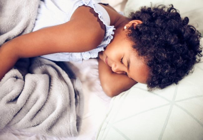 Young girl sleeping on white bed sheets with blanket