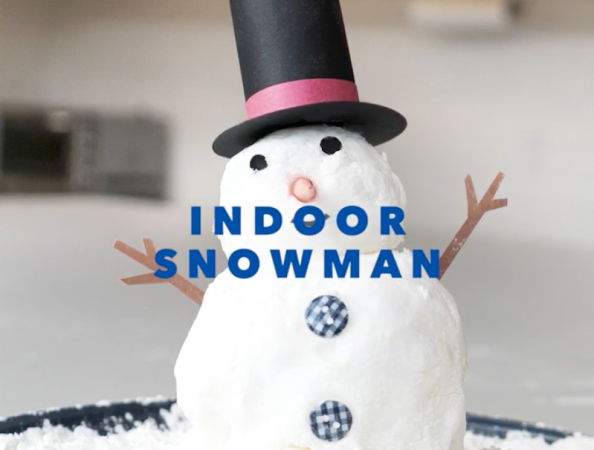 White indoor snowman made from whipped cream and cornstarch with blue text overlay reading