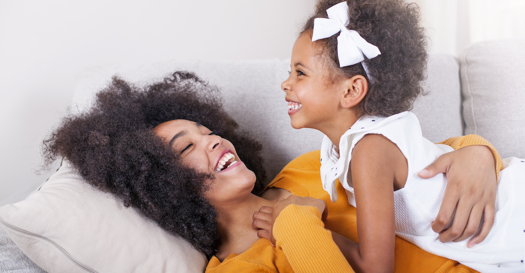 Mother and 3-year-old daughter laying on a bed, laughing and smiling.