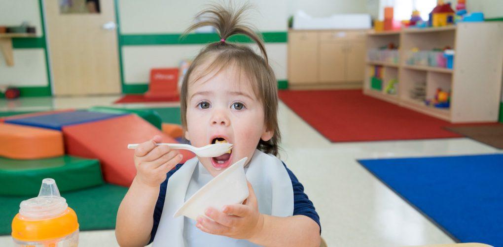 Preschooler eats healthy meal in classroom