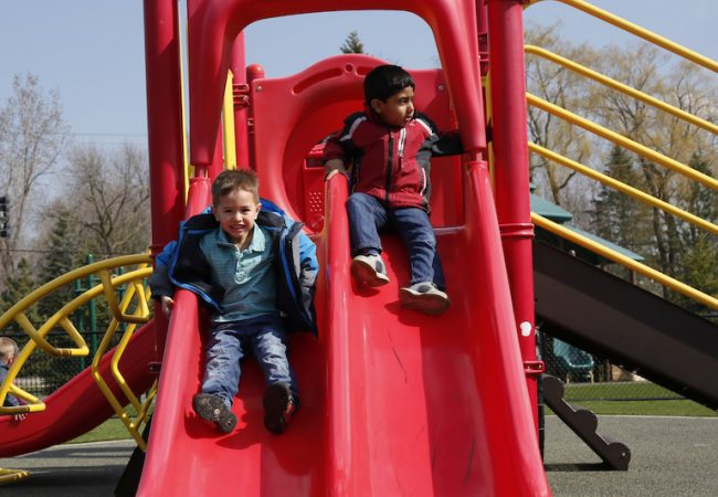 Primrose students smiling sliding down a slide, taking turns and learning Design Thinking