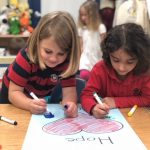 Preschool girls write card to accompany their Read Across America book donation
