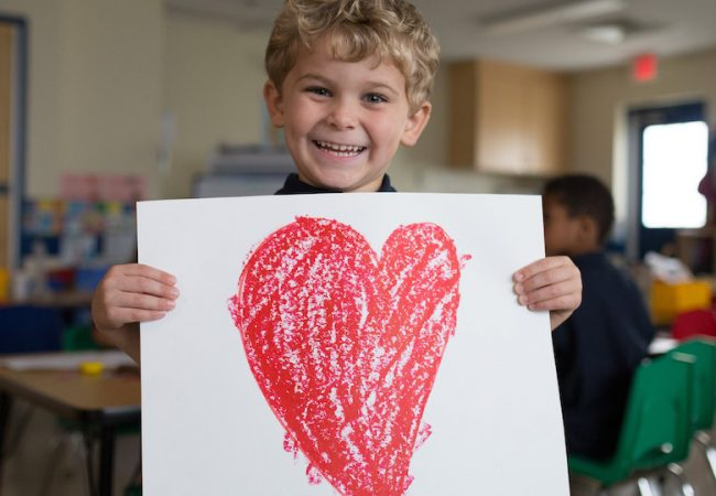 Primrose student smiles and holds white poster with red heart drawn on it