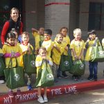 Preschool students smile holding book donations