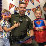 Preschool students dressed as superheroes smiles with local police officer