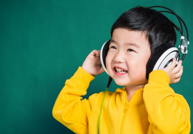 Preschool boy in yellow sweatshirt listens to kid's podcast