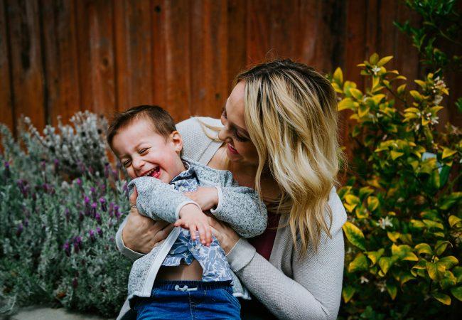 mom hugging smiling toddler