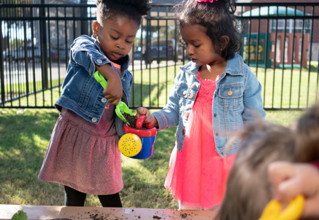 two girls using a watering can at the Primrose patch