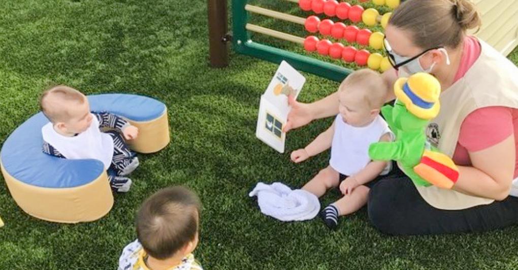 Teacher reading to infants outside